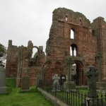 Lindisfarne gravestone and crumbling arches